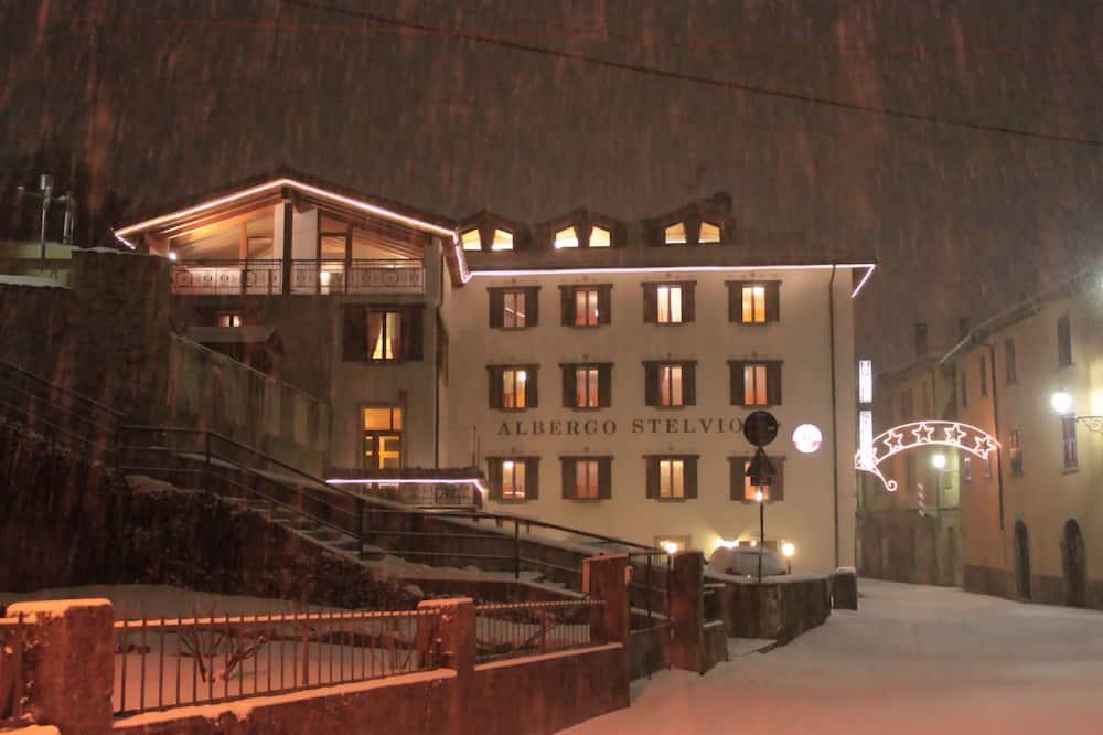 Průčelí hotelu ve dne/v noci