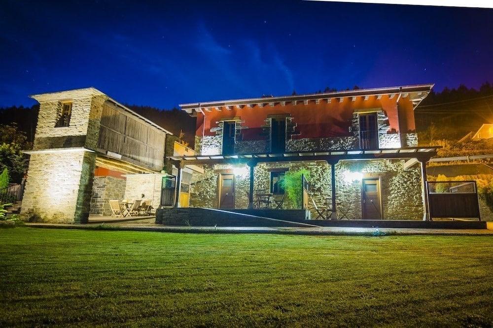 Vista frontal de la propiedad por la noche