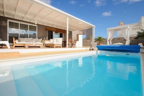 ゴルフコースの近くに豪華なプールとパティオエリアがあるエアコン完備のヴィラ